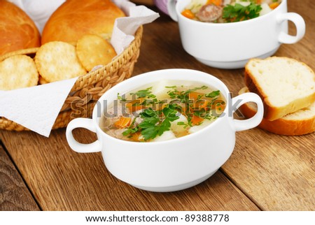 Homemade soup with meatballs on the kitchen table - stock photo