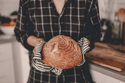 Homemade sourdough bread. Bright white kitchen. Bread on cutting board. Kitchen utensils. Craft authentic bread. Home cooking. Food preparation. Coronavirus covid-19 stay home isolation quarantine.