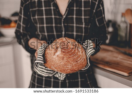 Homemade sourdough bread. Bright white kitchen. Bread on cutting board. Kitchen utensils. Craft authentic bread. Home cooking. Food preparation. Coronavirus covid-19 stay home isolation quarantine.
