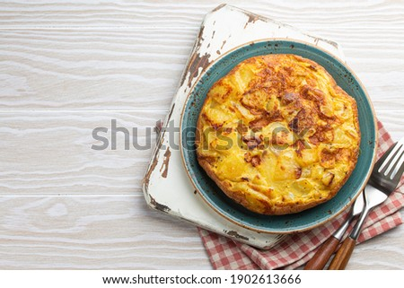 Homemade Spanish tortilla - omelette with potatoes on plate on white wooden rustic background top view. Traditional dish of Spain Tortilla de patatas for lunch or snack, overhead. Space for text Foto stock ©
