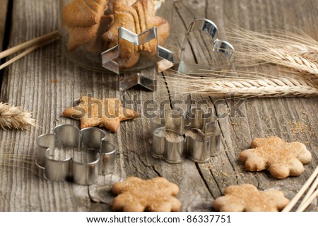 Homemade sugar cookies with metal cookie cutters and rye on old wooden table