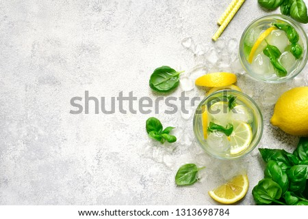 Homemade summer basil lemonade in a glasses over light slate, stone or concrete background.Top view with copy space.