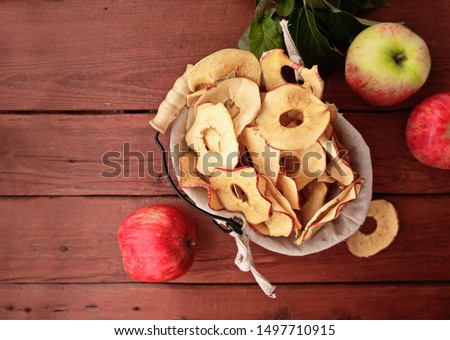 Homemade sun-dried organic apple slices, crispy apple chips, on an old rustic wooden table with fresh apple. Healthy snack. The concept is a healthy diet. Chips are part of a vegetarian diet. Top view #1497710915
