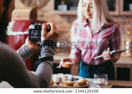 Homemade sweet bakery. Food photography. Man taking pictures of blonde woman with fresh cakes and pastries.