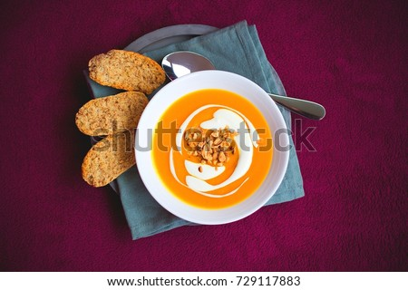 Homemade sweet potato and carrot soup with chili and ginger decorated by sour cream and roasted peanut in white bowl laying on the concrete tray with blue napkin with whole grain crackers Stock photo ©
