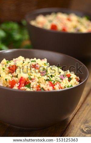 Homemade Tabbouleh, an Arabian vegetarian salad made of couscous, tomato, cucumber, onion, garlic, parsley and lemon juice served in brown bowls (Selective Focus, Focus one third into the tabbouleh)