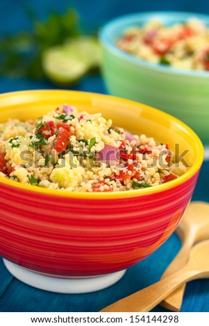 Homemade Tabbouleh, an Arabian vegetarian salad made of couscous, tomato, cucumber, onion, garlic, parsley and lemon juice served in colorful bowl (Selective Focus, Focus one third into the tabbouleh)