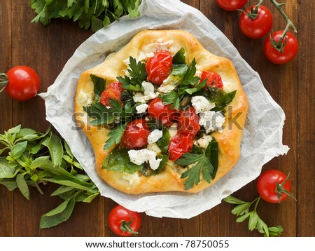 Homemade tart with cottage cheese, herbs and cherry tomatoes. Viewed from above.