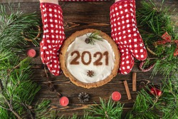 Homemade tart with the number 2021 on white cream. Wooden table decorated with pine branches and red decor for Christmas and new year