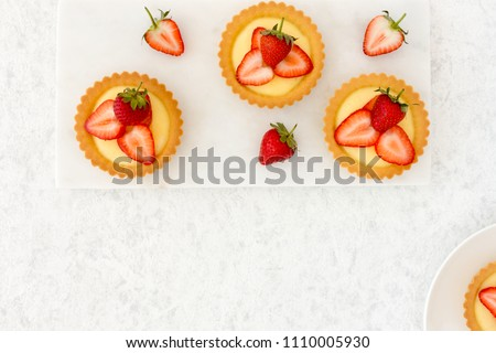 Homemade  tartlets filled with fresh strawberries and vanilla cream on white marble board and white marbled background.