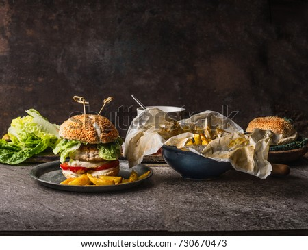 Homemade tasty burger with chicken, lettuce, mozzarella and tomatoes served with french fries potatoes on rustic kitchen table background with ingredients , front view