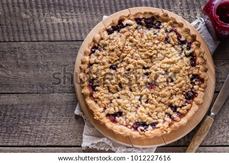 Homemade tasty shortcrust raspberry pie with crumble on old wooden table background. Top view, copy space