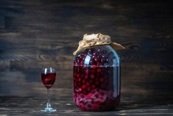 Homemade tincture of red cherry. Berry alcoholic drinks concept. Homemade red wine made from ripe cherries in a large glass jar and a wineglass on wooden background, Ukraine