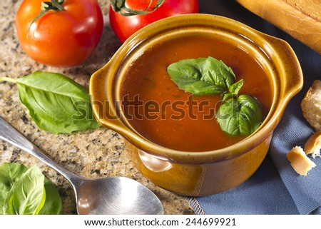 Homemade tomato and basil soup in the kitchen with fresh bread for dipping
