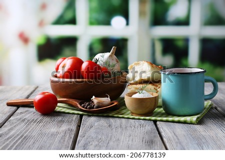 Homemade tomato juice in color mug, bread sticks, spices and fresh tomatoes on wooden table, on bright Foto stock ©