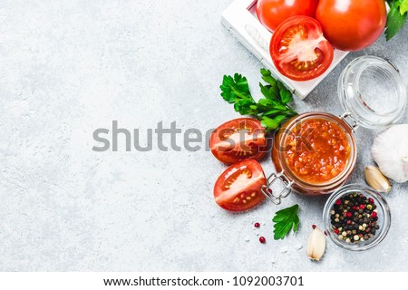 Homemade tomato sauce in glass jar with ingredients on concrete background. Top view, space for text.