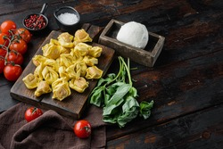 Homemade Tortellini with cheese and basil set, on wooden cutting board, on old dark wooden table background, with copy space for text
