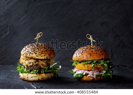 Homemade traditional and veggie burgers with beef, fried onion, sweet potato, radish and pea sprouts, served over black textured background. Healthy vs unhealthy concept food. Copy space