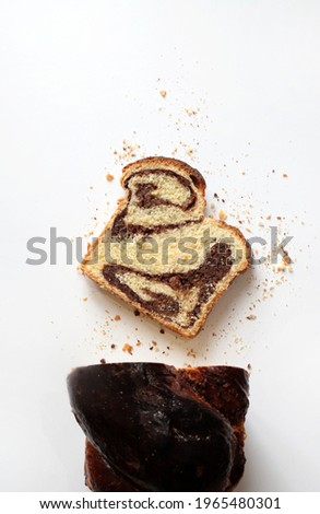 Homemade traditional Romanian sweet bread named 'cozonac', with cacao, raisins, and nuts on white background. Imagine de stoc ©