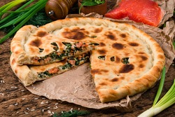 Homemade traditional tasty Ossetian pie with red fish, ossetian salmon pie