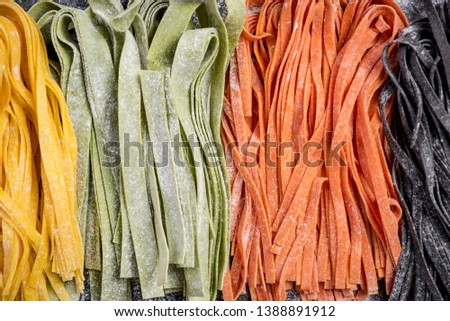 Homemade uncooked colorful tagliatelle pasta. Variety of colors. Dark slate background.
