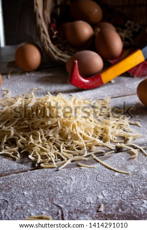 Homemade uncooked noodles on a wooden table