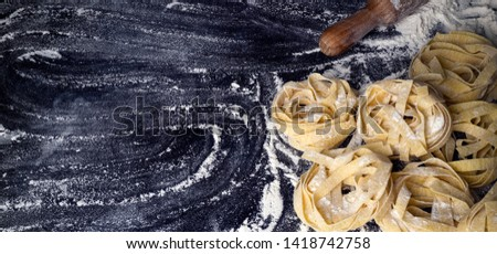 Homemade uncooked pasta on black background. Making fresh italian fettuccine. Copy space, banner