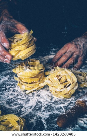 Homemade uncooked pasta on black background. Making fresh italian fettuccine. Vintage style