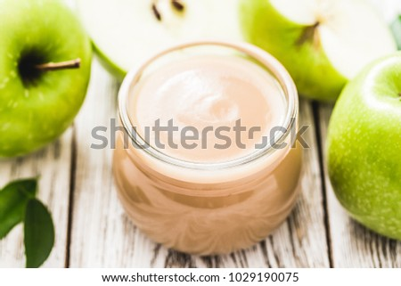Homemade unsweetened applesauce in glass jar and green apples on rustic white wooden background. Selective focus, space for text.  stock photo