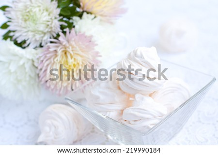Homemade vanilla zephyr with bouquet of asters. Selective focus
