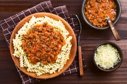 Homemade vegan bolognese sauce made with soy meat, fresh tomatoes, onion and garlic served on fusilli pasta on wooden plate, sauce and grated cheese on the side, photographed overhead