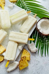Homemade vegan popsicles made with coconut milk and pineapple. Delicious healthy summer snack. Top view, flat lay.