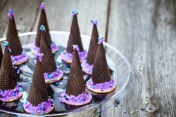 Homemade waffle cones cookies in the form of a Halloween witch hat decorated with purple icing on a wooden background. Selective focus on the hat. Also available in vertical format.