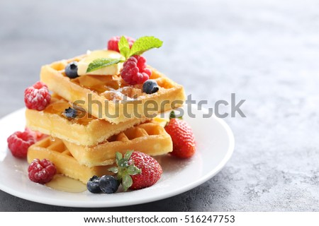 Homemade waffles with berries in plate on grey table