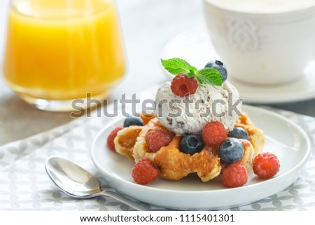 Homemade waffles with ice cream and fresh berries-raspberries, blueberries. Delicious dessert, cappuccino and orange juice on the table. Selective focus