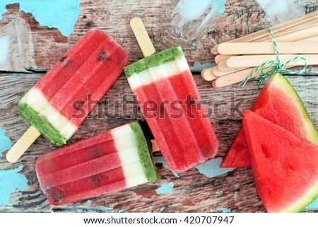 Homemade watermelon ice pops with melon slices against rustic wood background