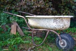 Homemade wheelbarrow from the bathtub. An old wheelbarrow from a baby bath and an airplane wheel.