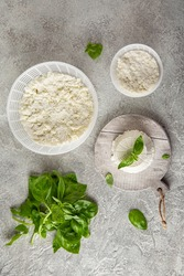 Homemade whey ricotta cheese or cottage cheese with basil ready to eat. Vegetarian healthy, nutritious diet food on a light background