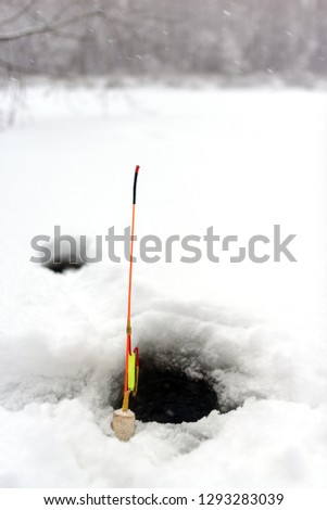 Homemade winter fishing rod stands at the hole in the ice of the river against the snow-covered forest. #1293283039