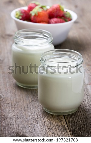 homemade yogurt in a glass jar and strawberry on a wooden background
