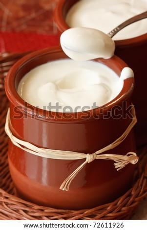 Homemade yogurt in a small ceramic pot.