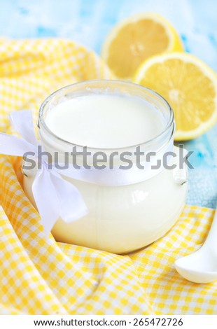 Homemade yogurt in small glass jar on a blue table, selective focus