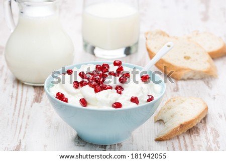 homemade yogurt with pomegranate, milk and bread on the wooden table
