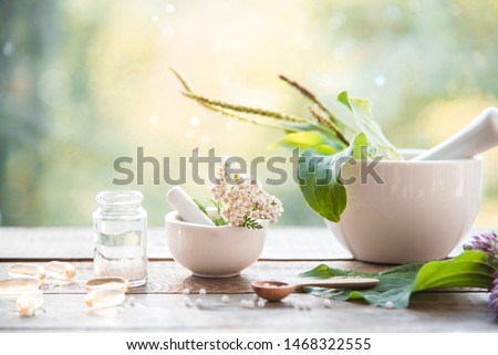 homeopathic granules, capsules and plants on a wooden table on a natural background. homeopathy, naturopathy and alternative medicine