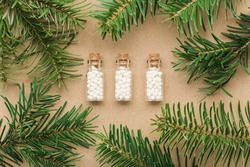 Homeopathic pills in glass bottles pine tree close up. Homeopathy, naturopathy and alternative medicine.