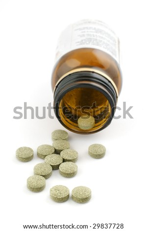 Homeopathic pills with bottle on white background