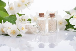 homeopathic pills with spring flowers on white background