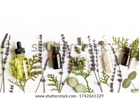 Homeopathy eco alternative medicine concept - classical homeopathy pills, thuja, eucalyptus, lavender essential and aroma oil and healing herbs and on white background. Flatlay. Top view. Copyspace Stock photo ©