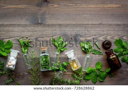 Homeopathy. Leaves of healing herbs, bottles and pills on wooden background top view copyspace Foto stock ©