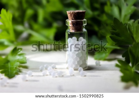 Homeopathy pills in vintage bottles on wood and green background. A bottle of homeopathic remedies. Herbal medicine, phytotherapy #1502990825